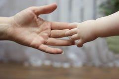 Dziecka ` s ręka dosięga do swój Obraz Stock