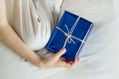 Dziecka ` s ręka w łóżkowych chwytach zaskakuje prezent Obraz Royalty Free