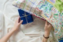 Dziecka ` s ręka w łóżkowych chwytach zaskakuje prezent Zdjęcie Royalty Free