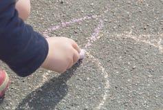 Dziecka ` s ręka z kredą, remis na bruku Obrazy Royalty Free