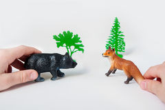 Dziecka ` s ręki bawić się z lasowymi zwierzęcymi postaciami na białym tle zdjęcie royalty free