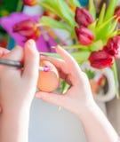 Dziecka ` s ręki dekoruje Wielkanocnego jajko Negatyw Przestrzeń Fotografia Stock