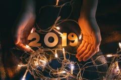 Dziecka ` s ręki na koc z błyszczącą girlandą i liczbami 2019, w wigilię nowego roku fotografia stock