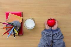 Dziecka ` s ręki trzyma czerwonego serce i notatnika z koloru mlekiem na drewna en stole i ołówkiem Zdjęcia Stock