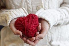 Dziecka ` s ręki trzymają serce czerwona nić dla dziać Zdjęcie Royalty Free