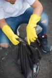 Dziecka ` s ręki w żółtych lateksowych rękawiczkach trzyma czarnego torba na śmiecie na asfaltowym tle Ekologii ochrony pojęcie obraz royalty free