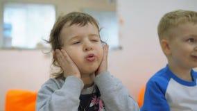Dziecka ` s rozwija gemowego pokój Emocje młode dzieci podczas zabawiać klasy Dzieci siedzą na krzesłach w a zbiory