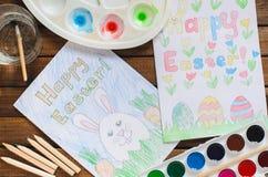Dziecka ` s rysunek na temacie wielkanoc: jajko, królik, gratulacje z wielkanocą Widok od wierzchołka, farby, ołówki, szczotkuje  Fotografia Stock