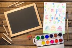 Dziecka ` s rysunek na temacie wielkanoc: jajko, królik, gratulacje z wielkanocą Widok od wierzchołka, farby, ołówki, szczotkuje  Zdjęcie Royalty Free
