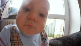 Dziecka ` s widok kamery zakończenie up strzelał Śliczny mały dziecko jest przyglądający w kamerę Dziecko próby lizać zbiory