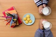 Dziecka ` s wręcza trzymać dojnych szkła i przekąskę z notatnikiem i koloru ołówkiem na drewnianym stole Odgórny widok Fotografia Stock