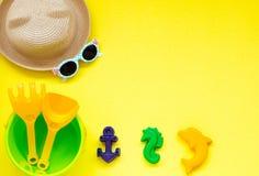 Dziecka ` s zabawki dla piaska na żółtym tle z kapeluszem i szkłami, przestrzeń dla kopii przestrzeni fotografia royalty free