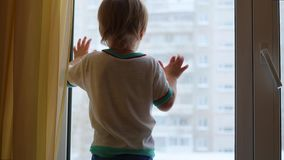 Dziecka stojaki na windowsill i przyglądający out okno zbiory wideo
