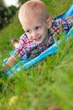 Dziecka szczęśliwy lying on the beach jest wśród zielonej trawy Zdjęcia Royalty Free
