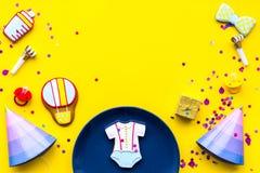 dziecka urodzonej chłopiec karty nowa prysznic Ciastka w kształcie akcesoria dla dziecka, partyjnych kapeluszy i confetti na żółt obraz stock