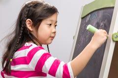 Dziecka Writing na Blackboard tle, dziecka Writing na/Blackboard, dziecka Writing na Blackboard na Białym tle/ Zdjęcie Stock
