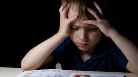 Dziecka zamyślenie czyta książkę w domu, siedzi przy stołem przed pora snu, zaświecającym lampą, trzyma jego ręki za jego