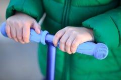 Dziecko łęki utrzymują kierownicy hulajnoga Fotografia Stock