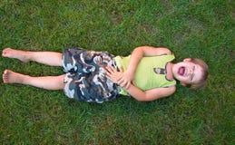 Dziecko śmia się, kłamający na trawie zdjęcia royalty free