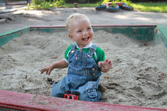 Dziecko śmia się podczas gdy bawić się w piaskownicie z piaskiem Zdjęcia Stock