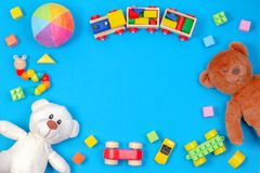 Dziecko ?artuje zabawki t?o Dwa misia, drewniany poci?g, zabawkarscy samochody, kolorowi bloki na b??kitnym tle obrazy stock