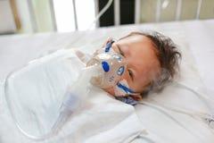 Dziecko astmy i potrzeby nebulizations, Chorej ch?opiec inhalacyjna terapia mask? inhalator Ch?opiec nosowego przekrwienie Dzieck zdjęcie royalty free