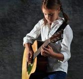 Dziecko bawić się gitarę przeciw grunge rujnującej ścianie Obrazy Royalty Free