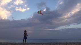 Dziecko Bawić się Latającą kanię na plaży, zmierzch, dziewczyna na linii brzegowej, słońce promienie 4K zbiory wideo