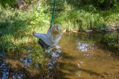 Dziecko bawić się na drzewo huśtawce nad wodą Obrazy Royalty Free