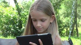 Dziecko Bawić się pastylki chlanie, dziewczyna Używa Internetowy Plenerowego w podwórze ogródzie 4K zbiory wideo