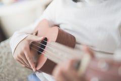 Dziecko bawić się ukulele Zdjęcia Royalty Free