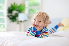Dziecko bawić się w łóżku żartuje pokój Chłopiec w domu fotografia stock