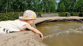 Dziecko bawić się w fontannie przy miasto parkiem na pogodnym letnim dniu zbiory