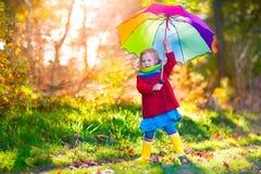 Dziecko bawić się w jesień dżdżystym parku Fotografia Stock