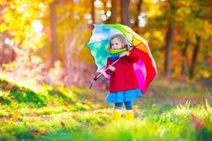 Dziecko bawić się w jesień dżdżystym parku Zdjęcie Stock