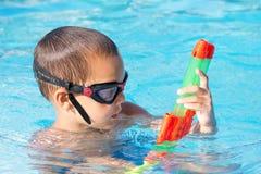 Dziecko bawić się w pływackim basenie z wodnym pistoletem Zdjęcia Stock
