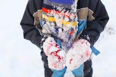 Dziecko bawić się z śniegiem w zimie Zdjęcia Stock