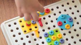 Dziecko bawić się z śrubowym zestawem zbiory