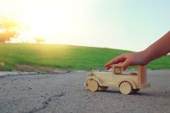 Dziecko bawić się z drewnianym zabawkarskim samochodem na drodze outdoors w parku obrazy royalty free