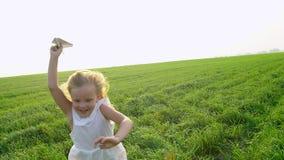 Dziecko bawić się z papierowym samolotem Ona śmia się i smilling Mała śliczna szczęśliwa dziewczyna w polu z papierem zbiory