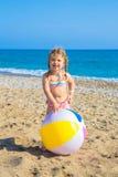 Dziecko bawić się z piłką na plaży fotografia stock