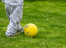 Dziecko bawić się z piłką w trawie obrazy stock
