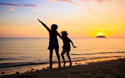 Dziecko bawi? si? na ocean pla?y Dzieciak przy zmierzchu morzem obrazy royalty free