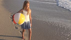 Dziecko Bawi? si? na pla?y przy zmierzchem, Szcz??liwy dzieciaka odprowadzenie w morzu Macha dziewczyny na nadmorski zbiory