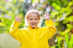 Dziecko bawi? si? w deszczu Dzieciak z parasolem zdjęcia stock