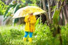 Dziecko bawi? si? w deszczu Dzieciak z parasolem zdjęcie stock