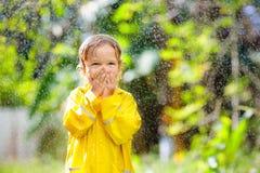 Dziecko bawi? si? w deszczu Dzieciak z parasolem zdjęcie royalty free