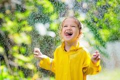 Dziecko bawi? si? w deszczu Dzieciak z parasolem fotografia stock