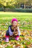 Dziecko bawić się z żółtymi liśćmi Obraz Royalty Free