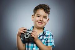 Dziecko bierze obrazek używa retro rangefinder kamerę odizolowywał popielatego tło Obrazy Stock
